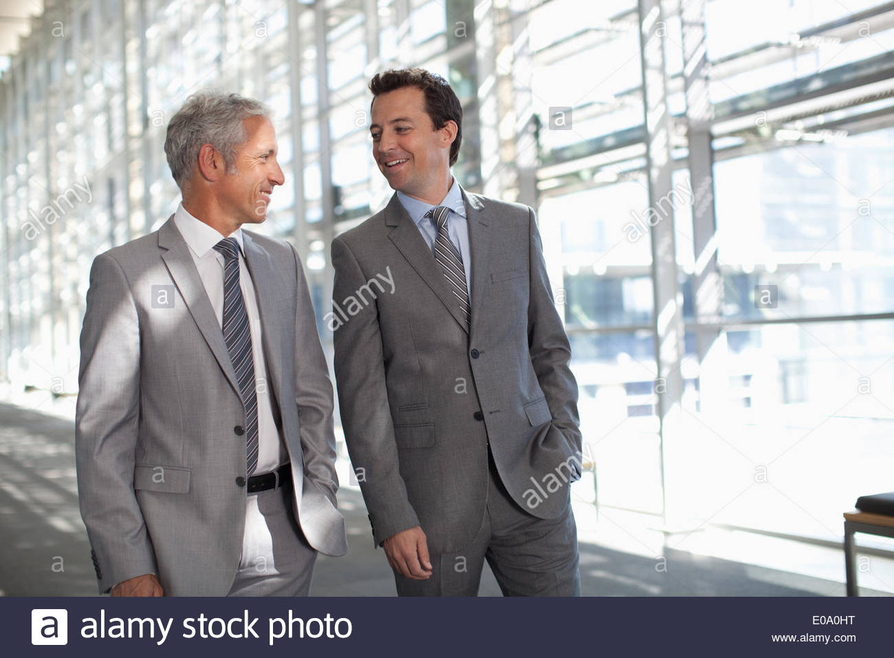 Two businessmen talking in modern lobby - Stock Image