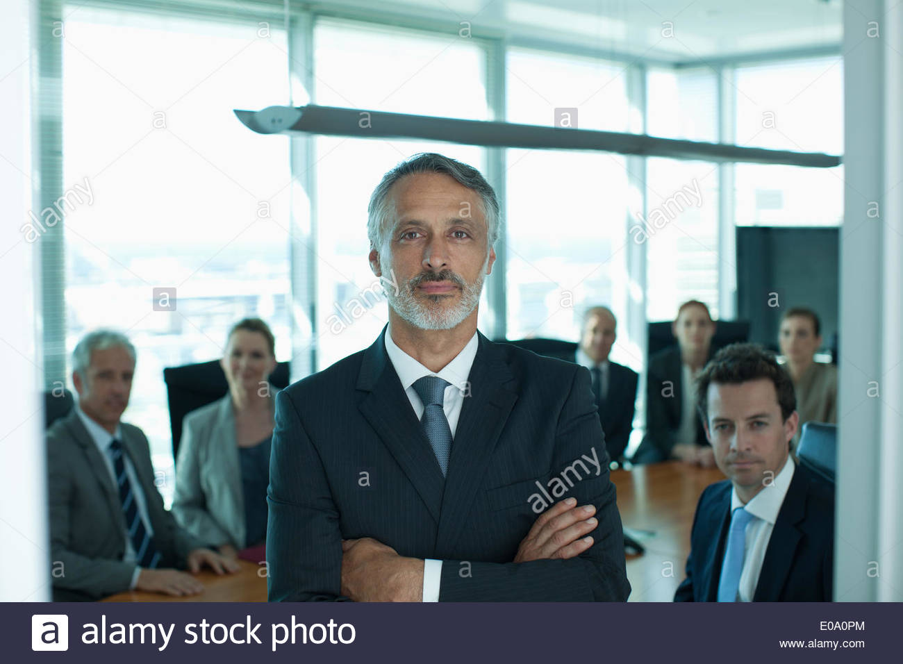Portrait of businessman and co-workers in conference room - Stock Image