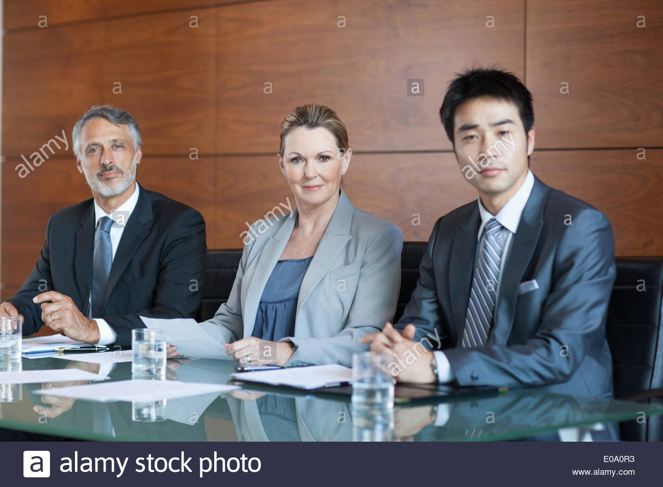 Businesswoman showing paperwork to businessmen in meeting - Stock Image