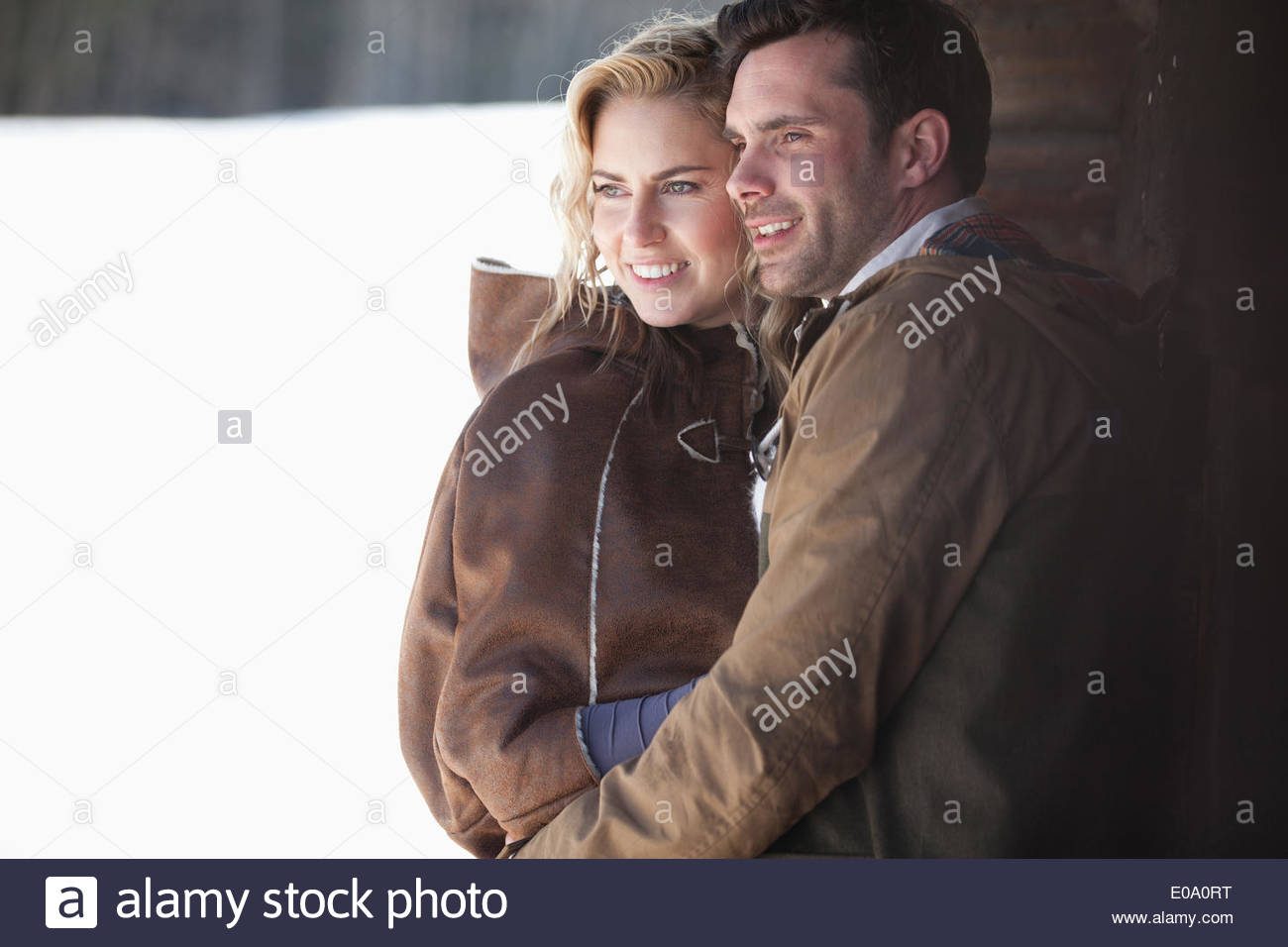 Smiling couple hugging in snow - Stock Image