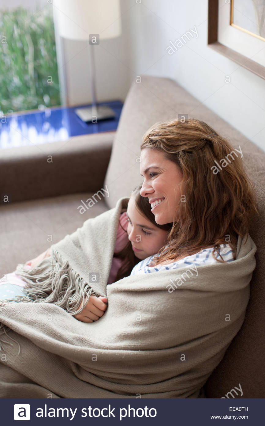 Mother and daughter wrapped in blanket on couch - Stock Image