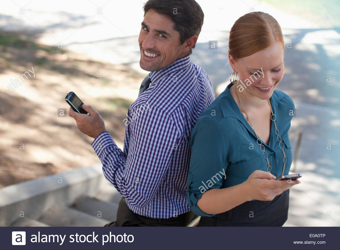 Business people using cell phones outdoors - Stock Image