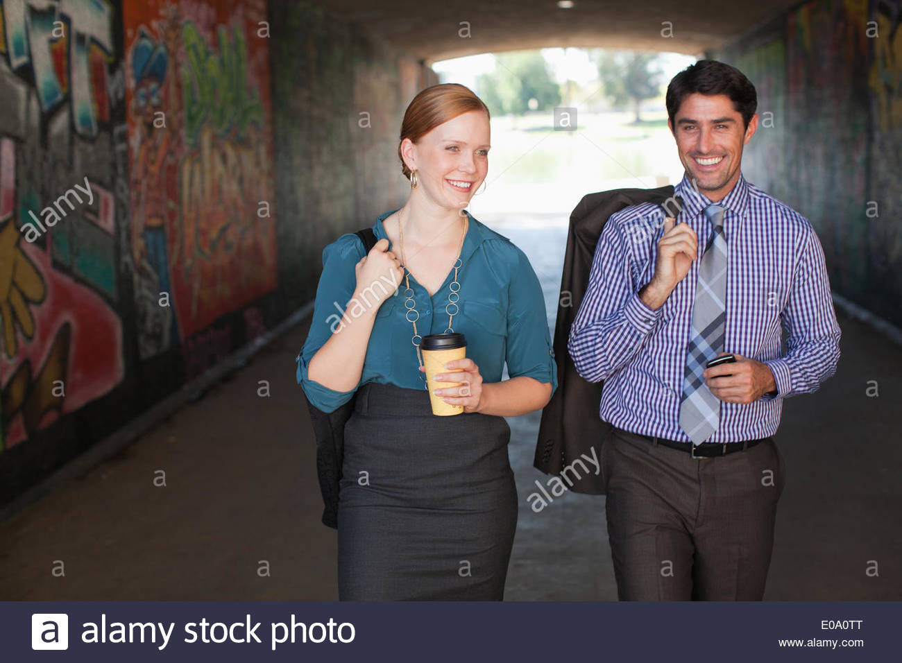 Business people walking together in tunnel - Stock Image
