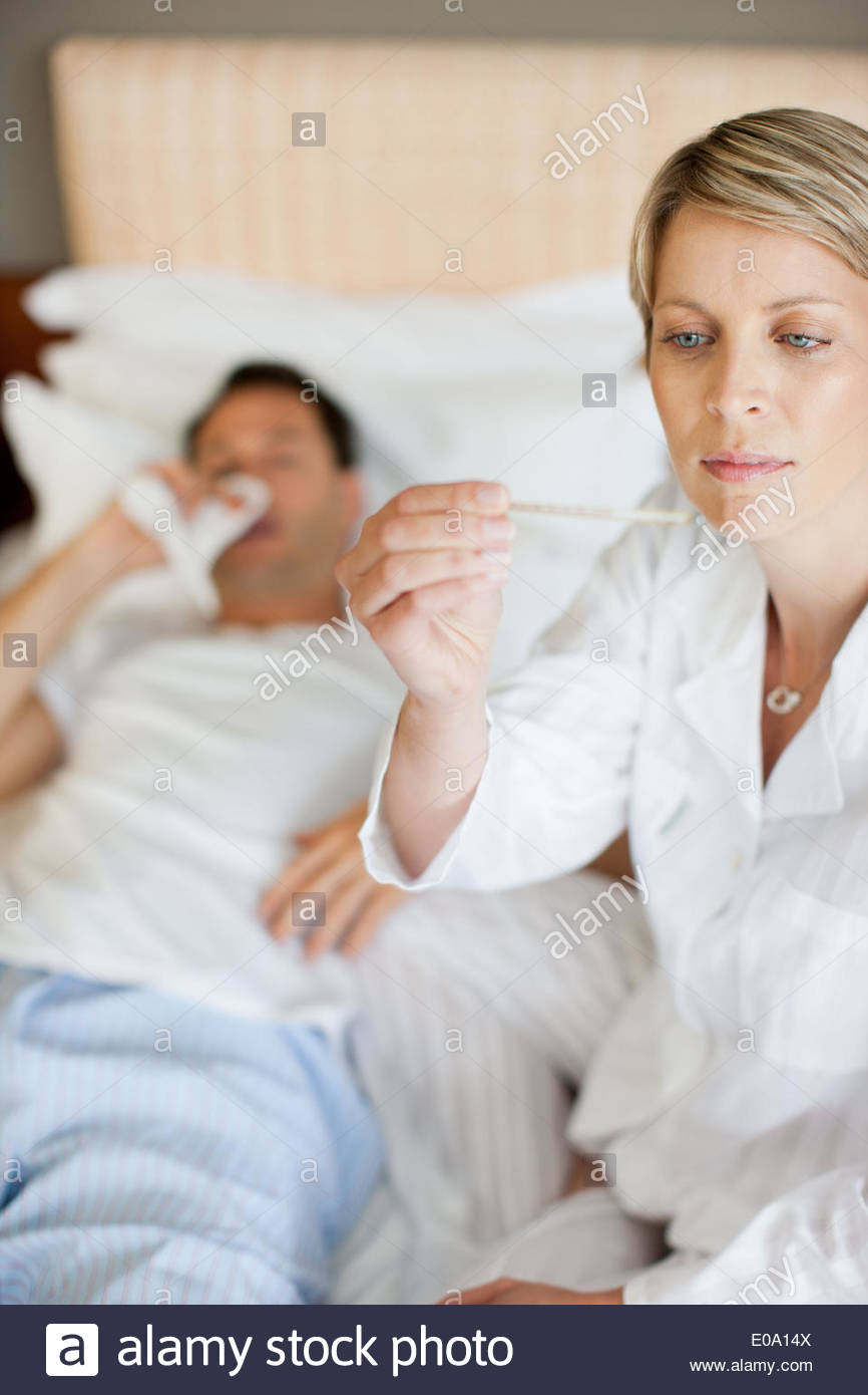 Wife taking wifeÂ's temperature - Stock Image