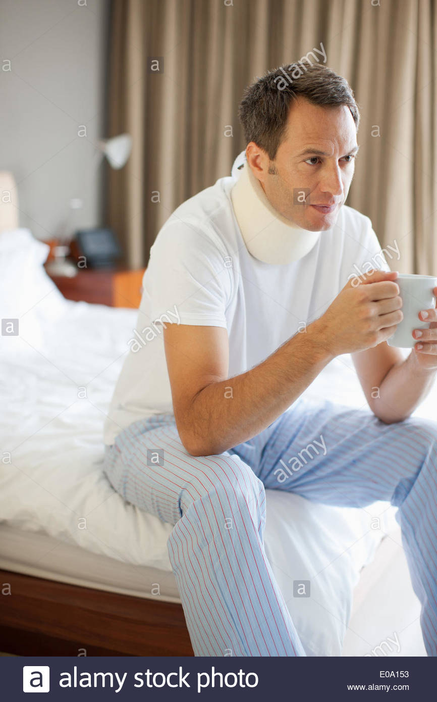 Man sitting on bed with neck brace drinking coffee - Stock Image