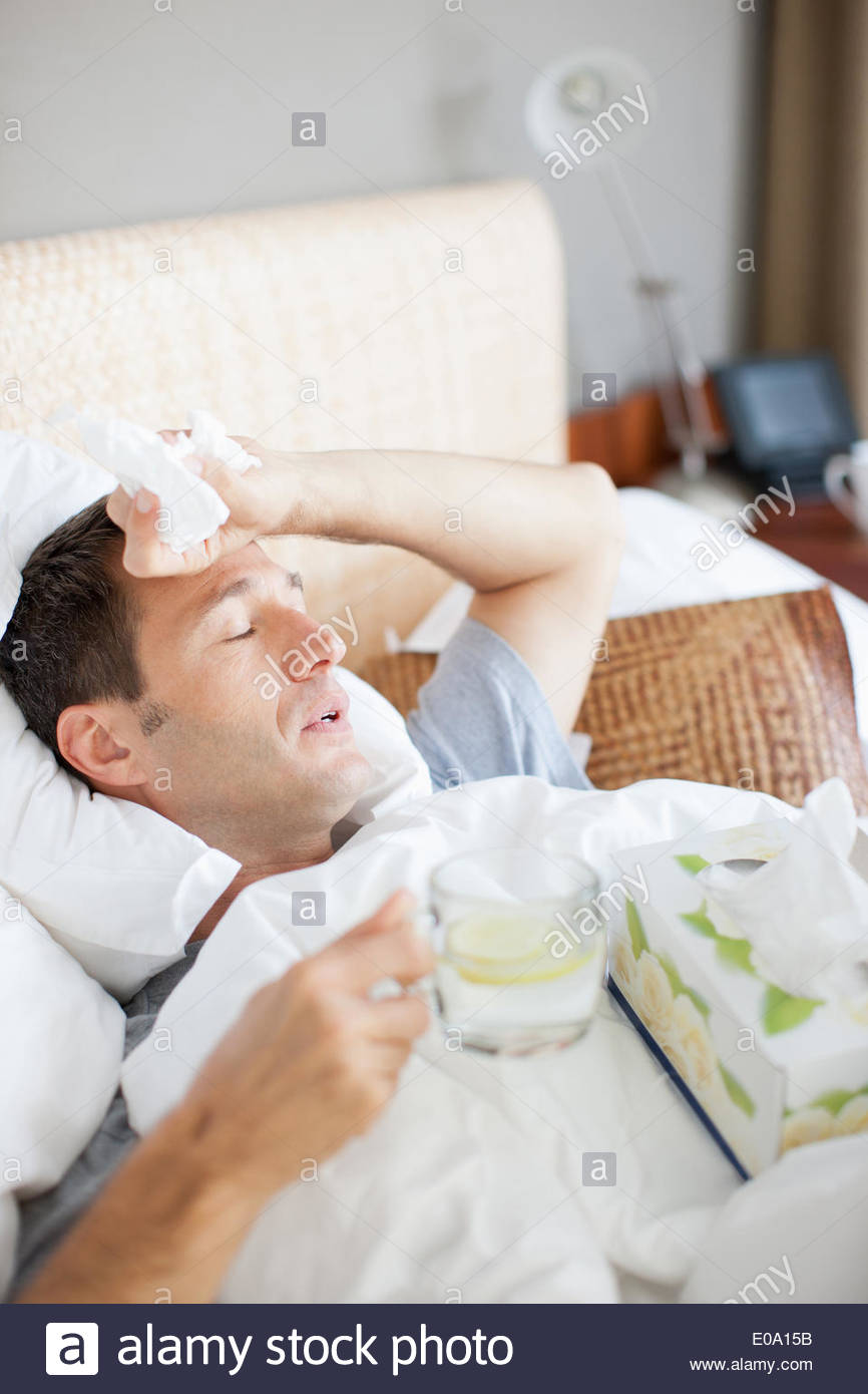 Man sick in bed drinking hot drink - Stock Image