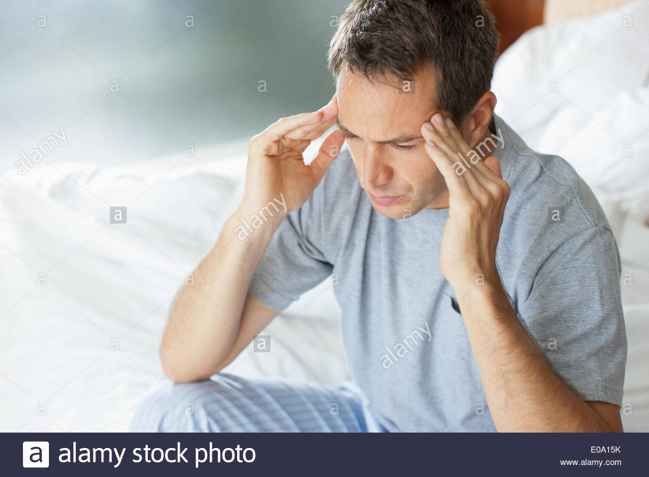 Man with headache rubbing forehead - Stock Image