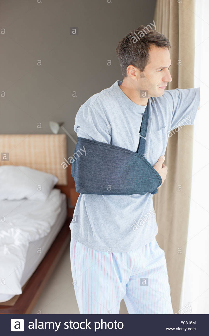 Man with broken arm looking out window - Stock Image