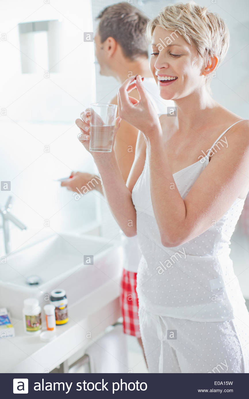 Woman taking vitamins in the morning - Stock Image
