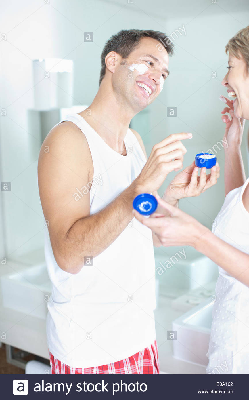Woman putting face cream on husbandÂ's face - Stock Image