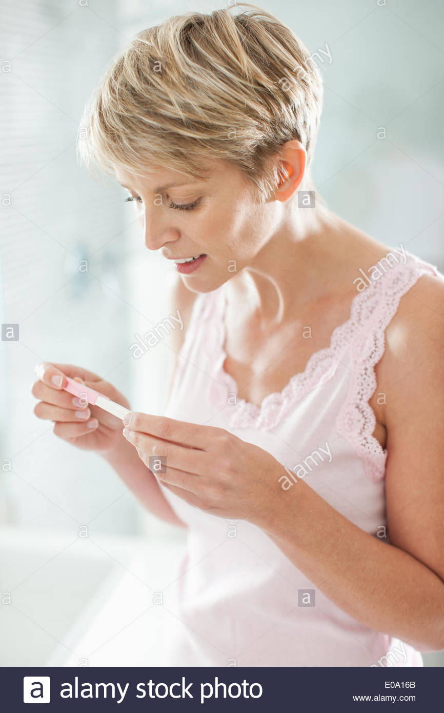 Happy woman looking at pregnancy test - Stock Image