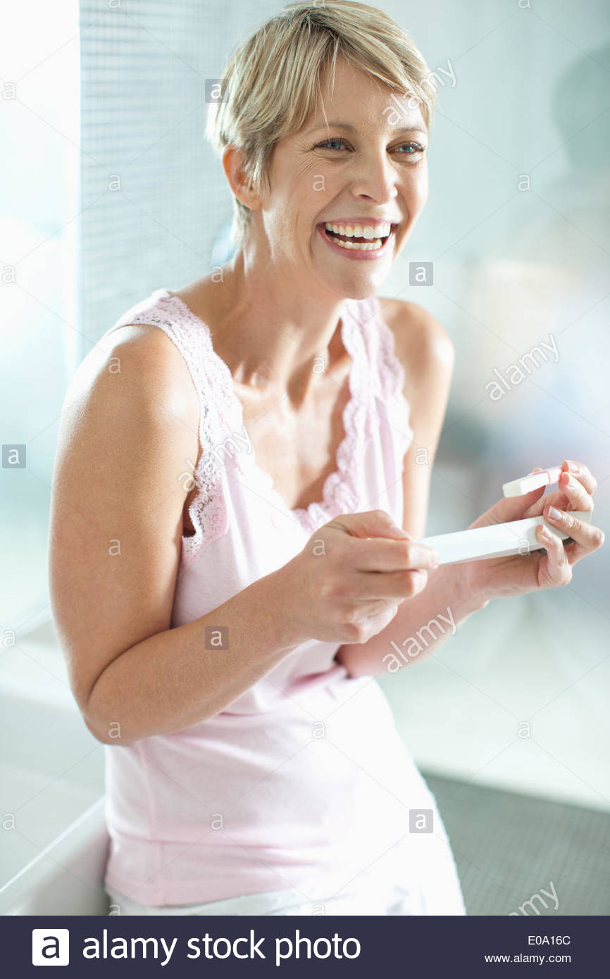 Excited woman looking at pregnancy test - Stock Image