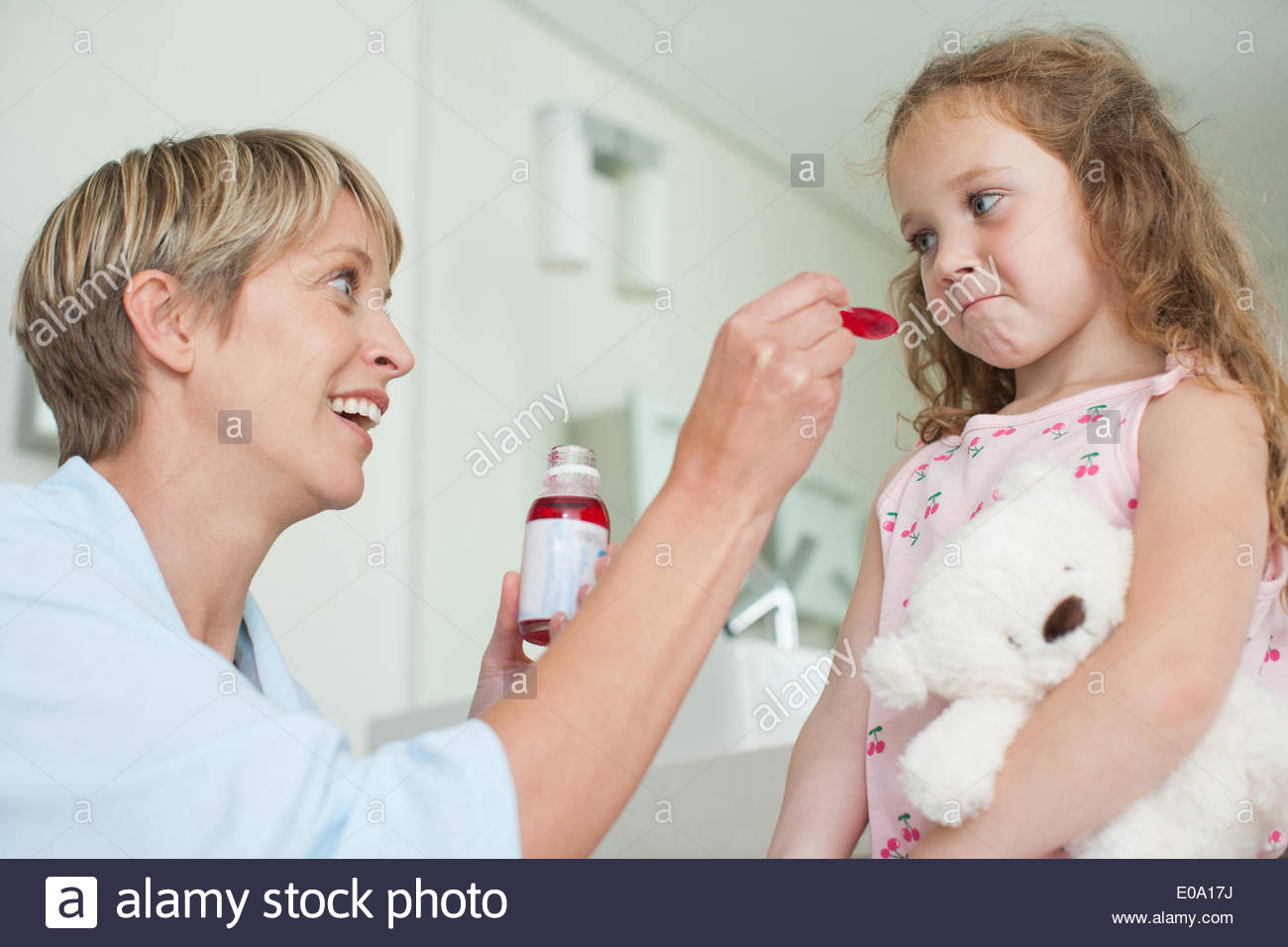 Mother giving daughter medicine - Stock Image