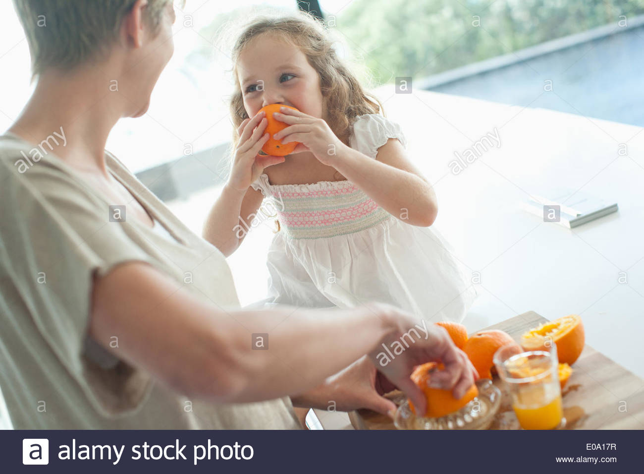 Mother watching girl eating orange - Stock Image