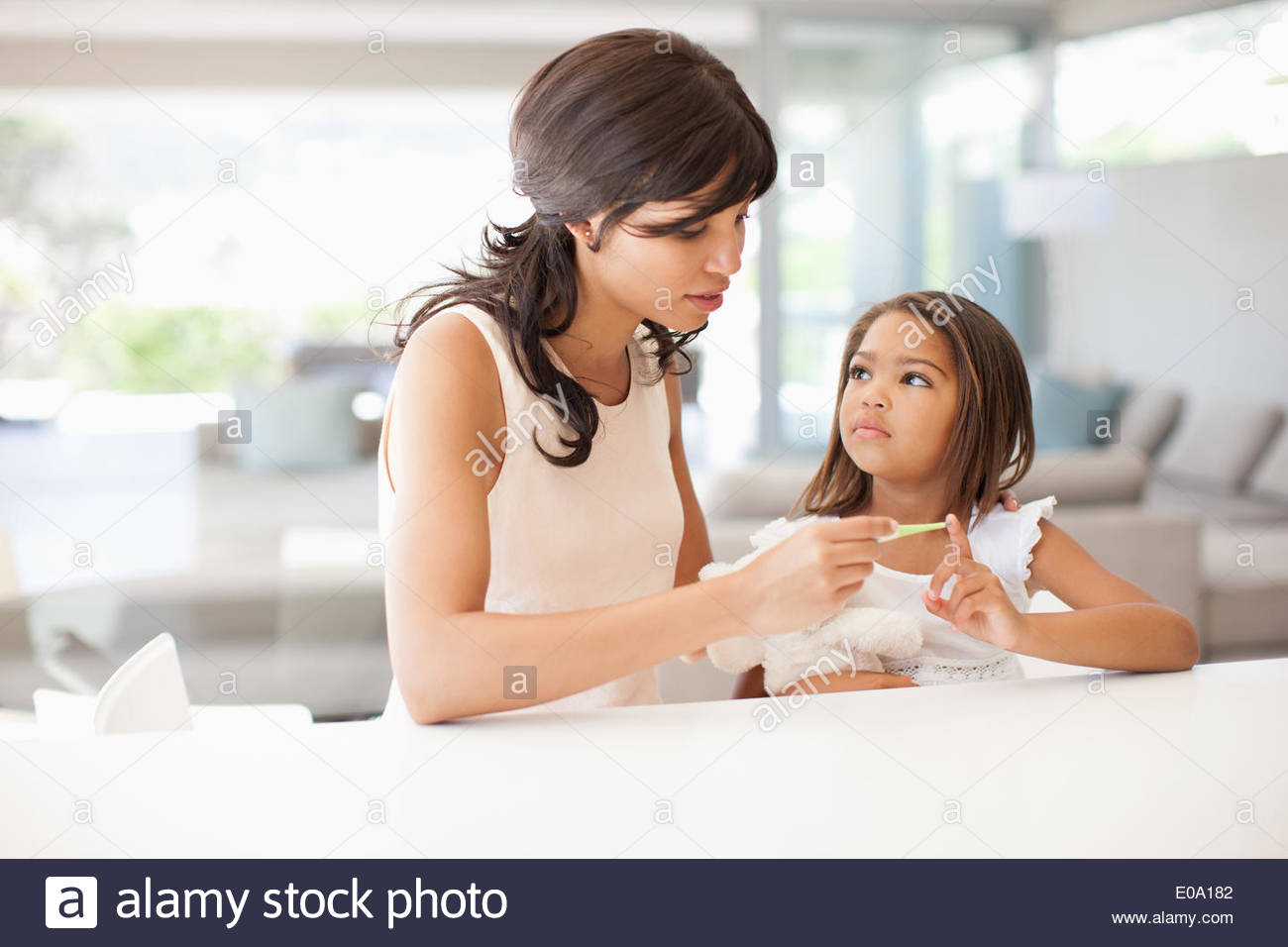 Mother taking daughterÂ's temperature - Stock Image