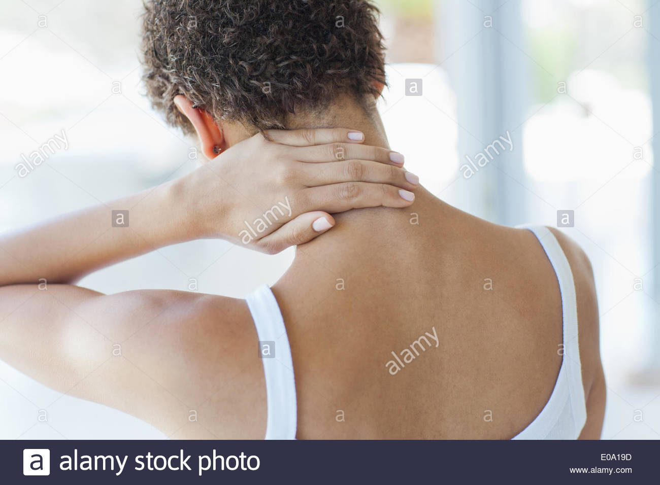 Woman rubbing sore neck - Stock Image