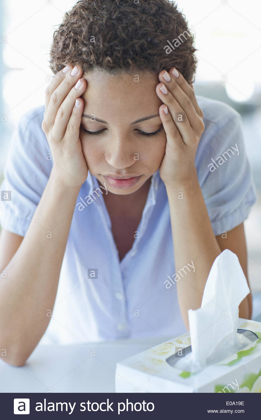 Woman with headache holding head - Stock Image