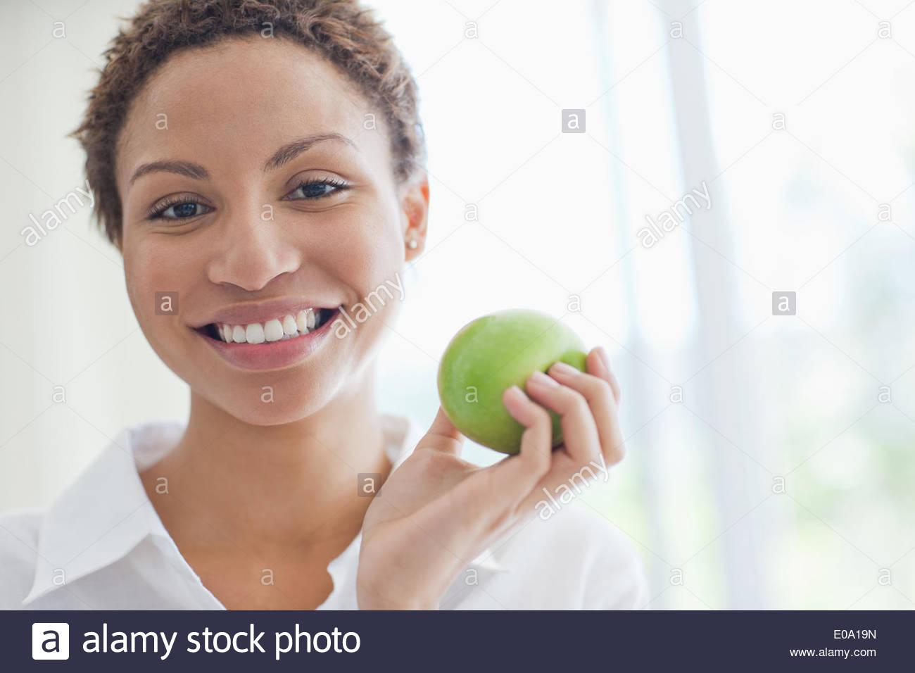 Woman eating green apple - Stock Image