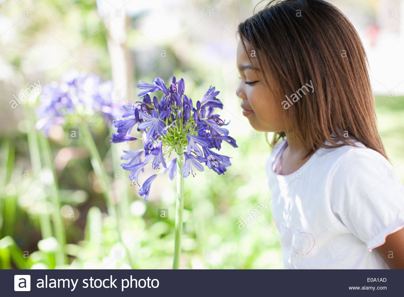 Girl smelling flower outdoors, portrait - Stock Image