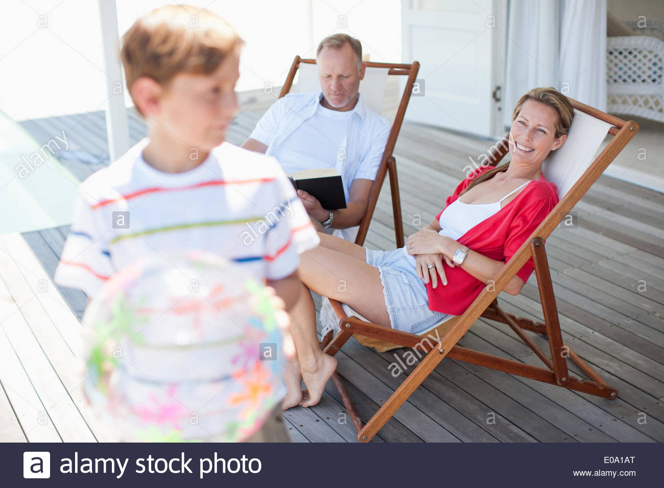Parents watching son play with ball on deck - Stock Image