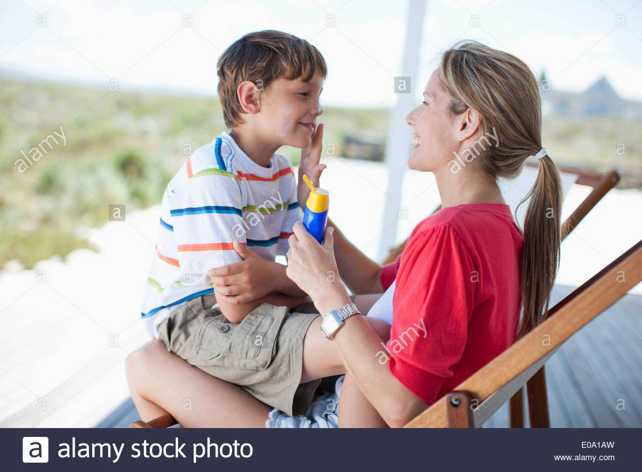 Mother putting sunscreen on boy - Stock Image