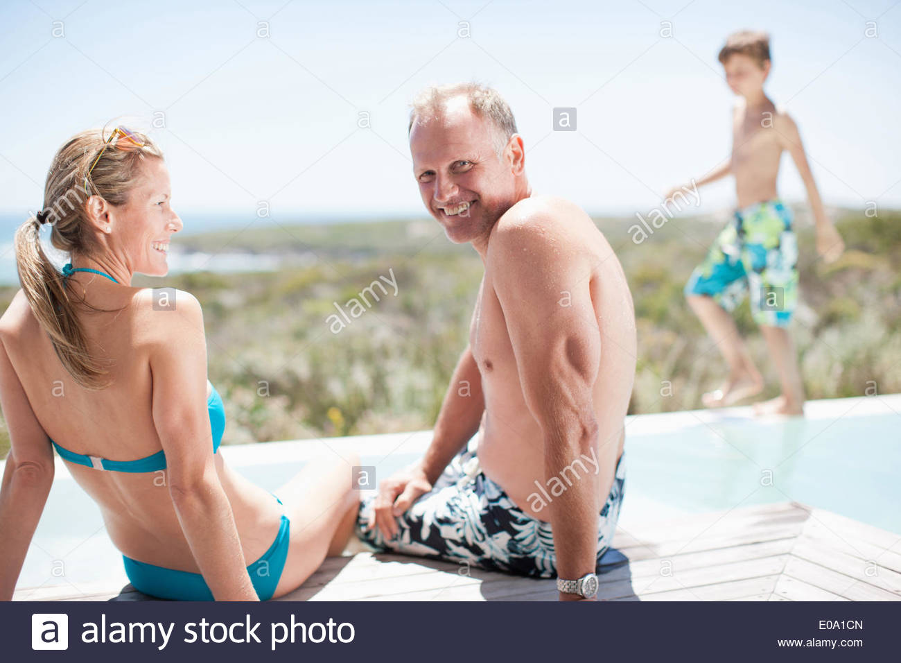 Family sitting by swimming pool - Stock Image