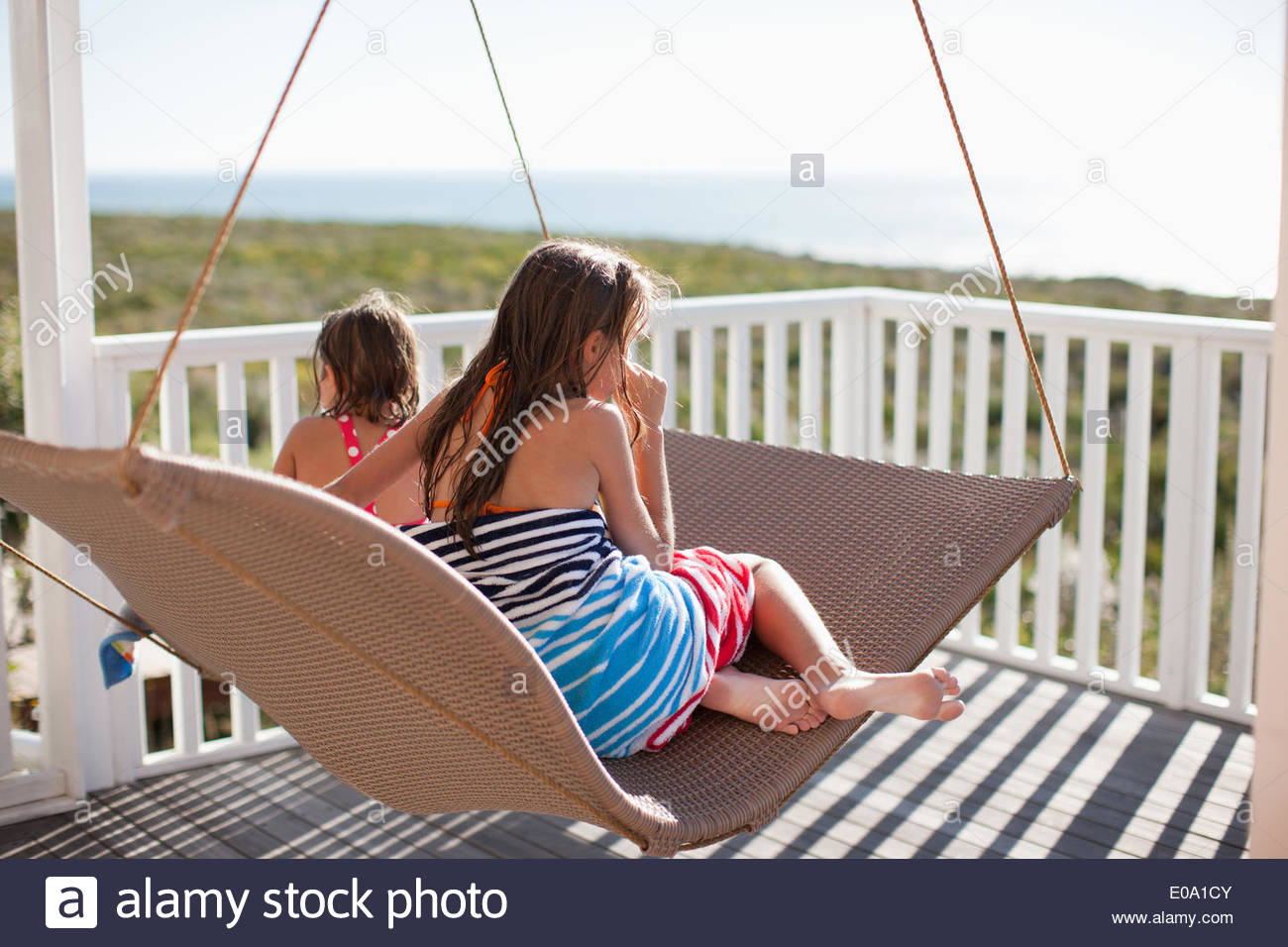 sisters relaxing on lounge chair on deck - Stock Image