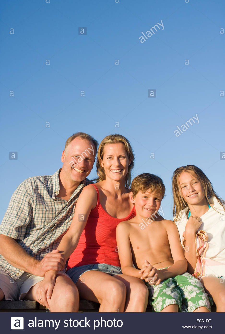 Family sitting on pier together - Stock Image