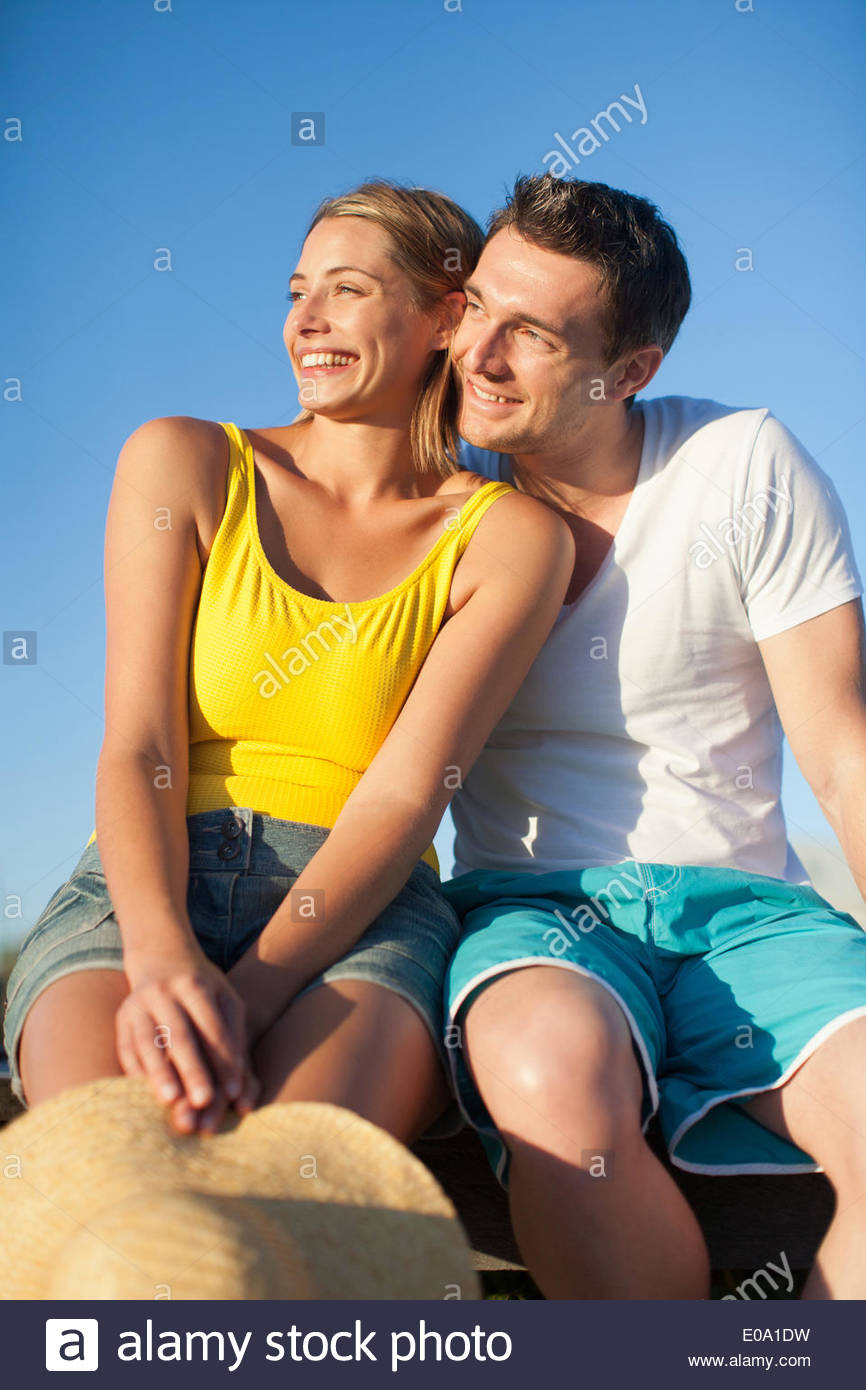 couple sitting on pier together - Stock Image