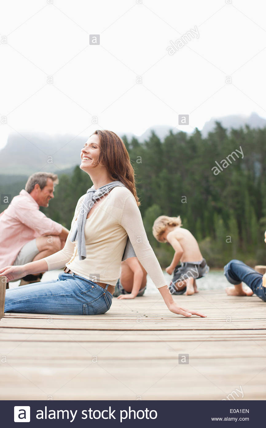 Family sitting on pier by lake - Stock Image