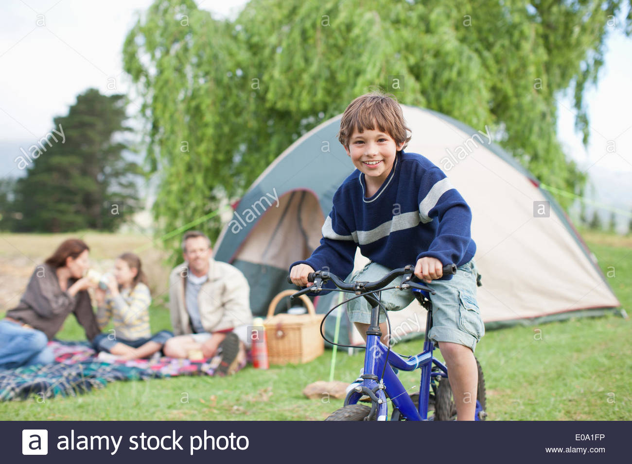 boy on bicycle while on family camping trip stock photo 69062218