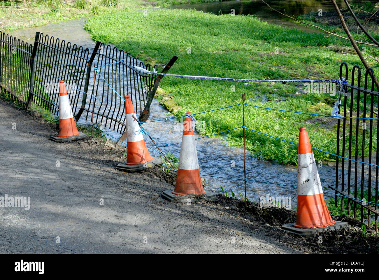 Traffic cones temporarily marking off damaged railings by a stream after a car accident. Loose Village, Kent - Stock Image