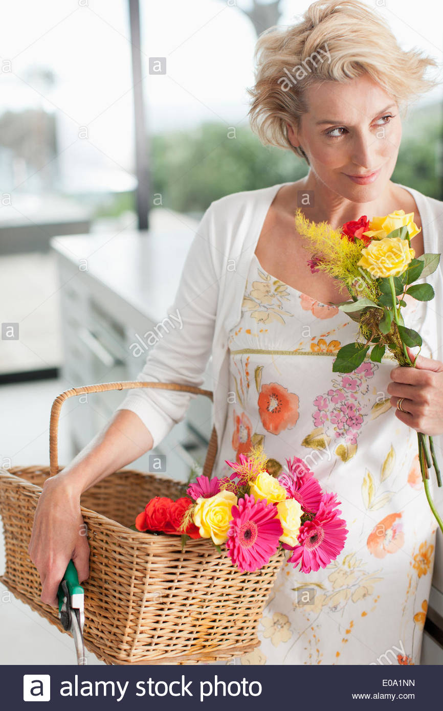 Mature woman with basket of flowers Stock Photo