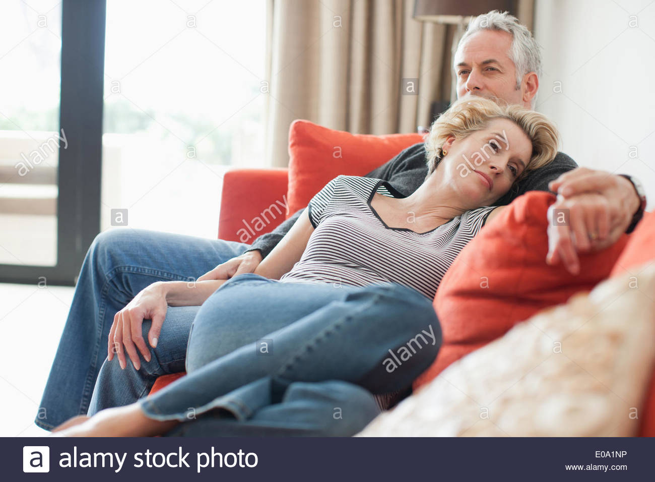 Mature couple laying on sofa holding hands - Stock Image
