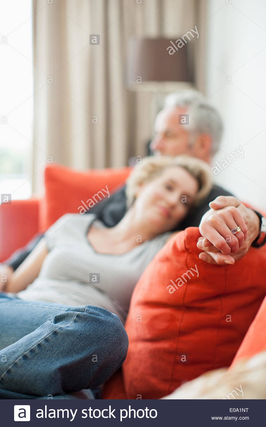 Mature couple laying on sofa holding hands Stock Photo