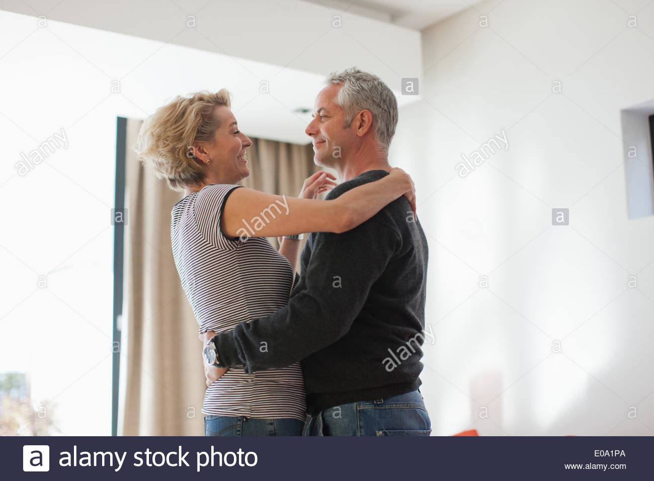 Mature couple dancing in living room Stock Photo