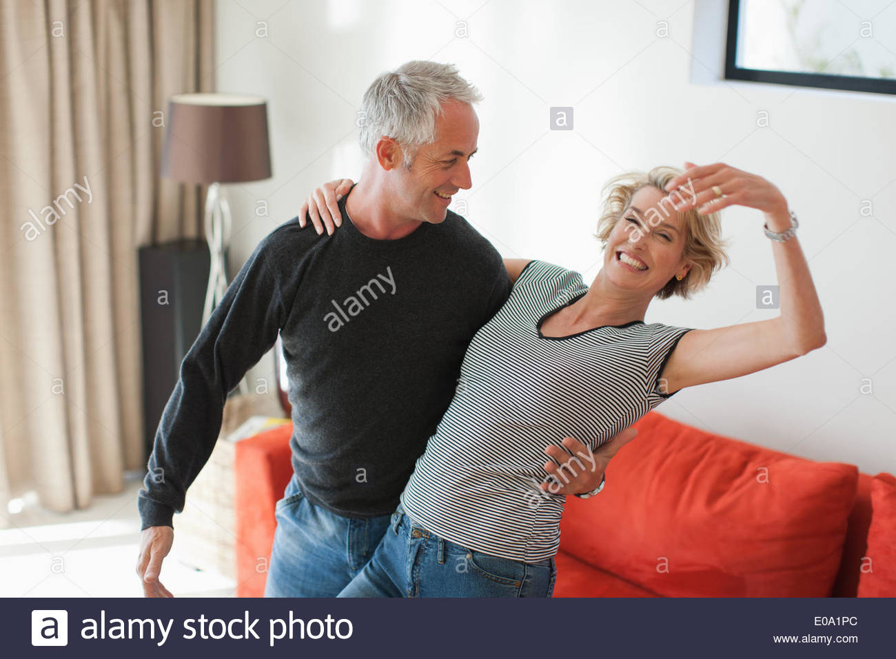 Mature couple dancing in living room - Stock Image