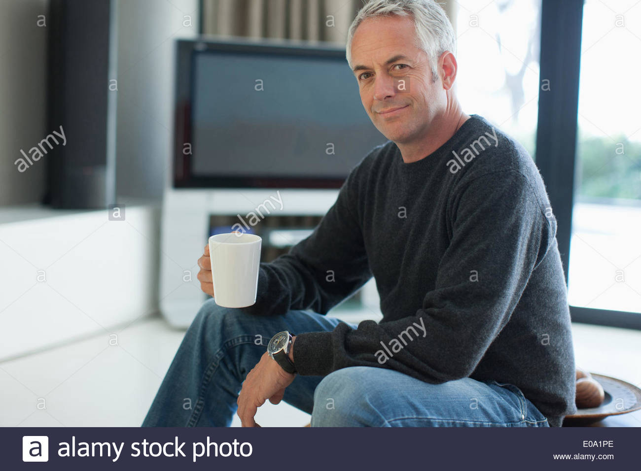 Man drinking coffee in living room - Stock Image