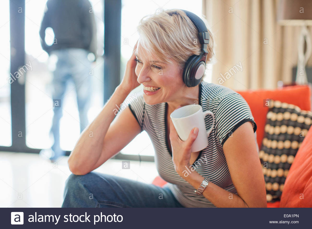 Woman drinking coffee and listening to headphones - Stock Image