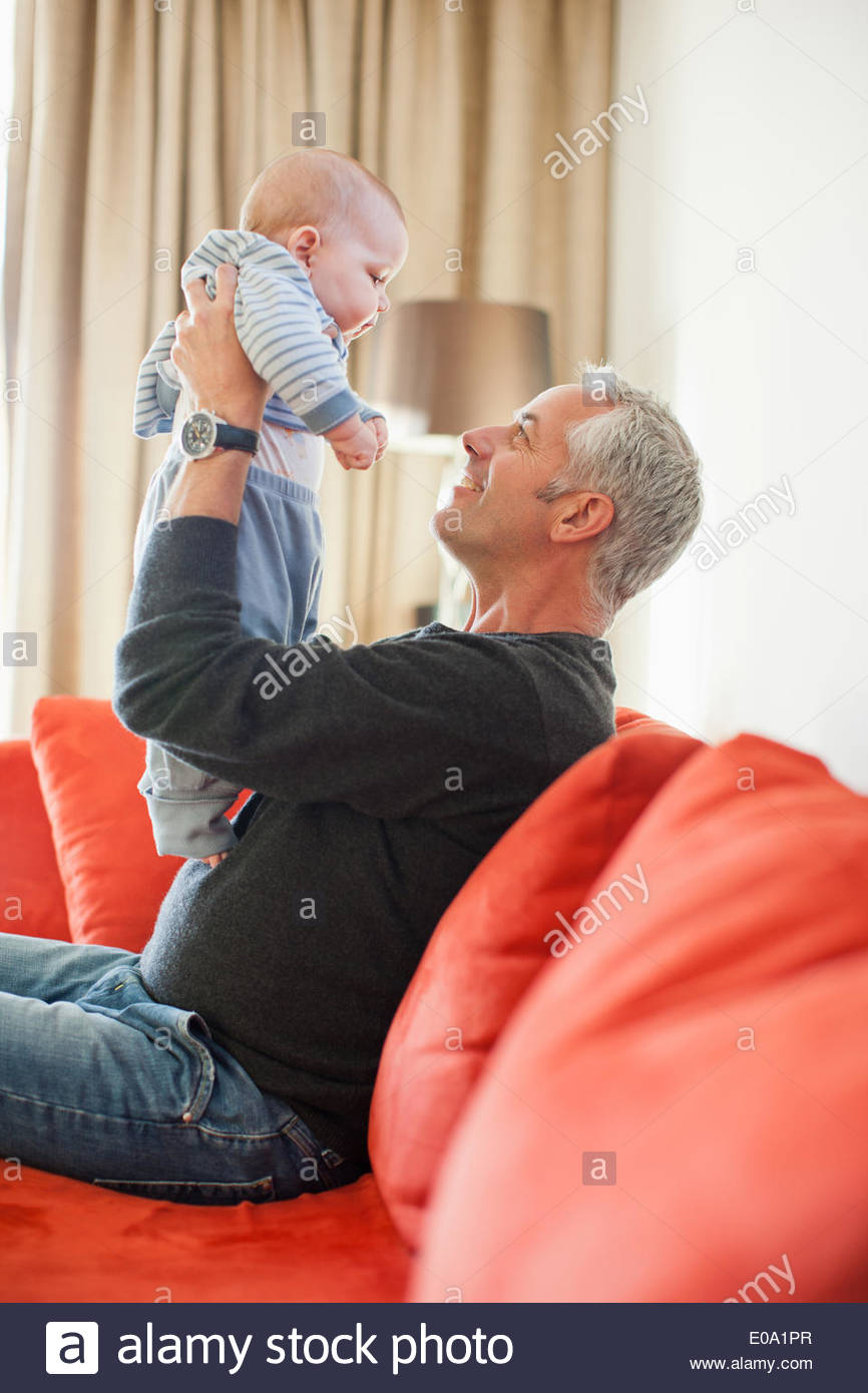 Man holding baby boy on lap - Stock Image