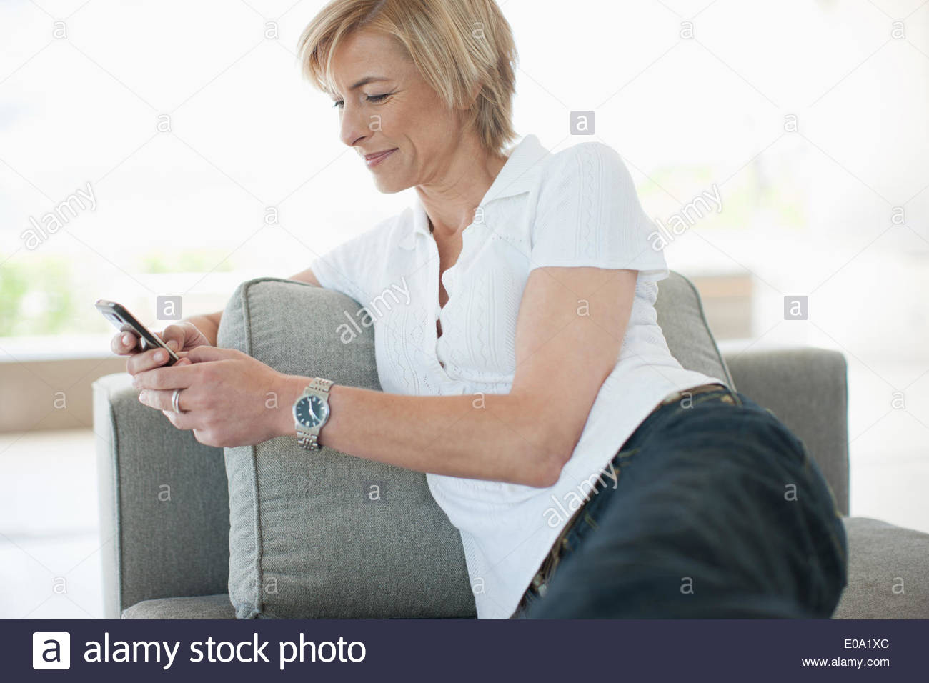 Woman text messaging on cell phone - Stock Image