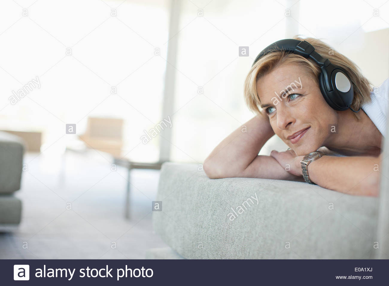 Woman laying on sofa listening to headphones - Stock Image