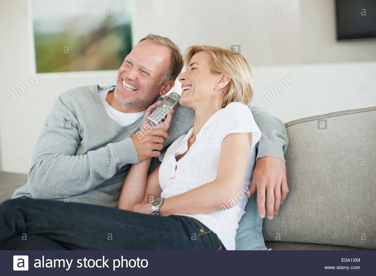 Couple listening to cordless phone together - Stock Image
