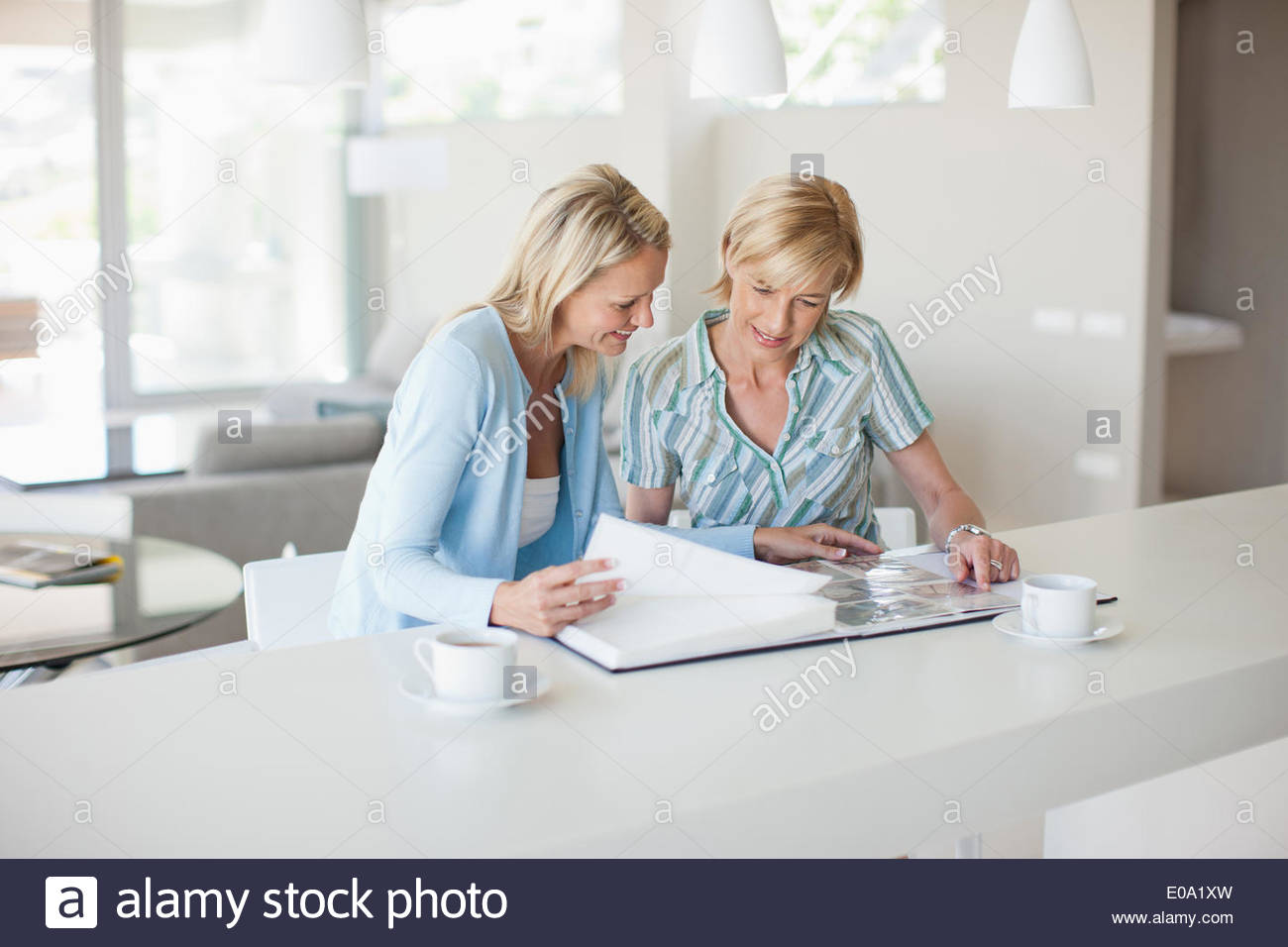 Friends looking at photo album together - Stock Image