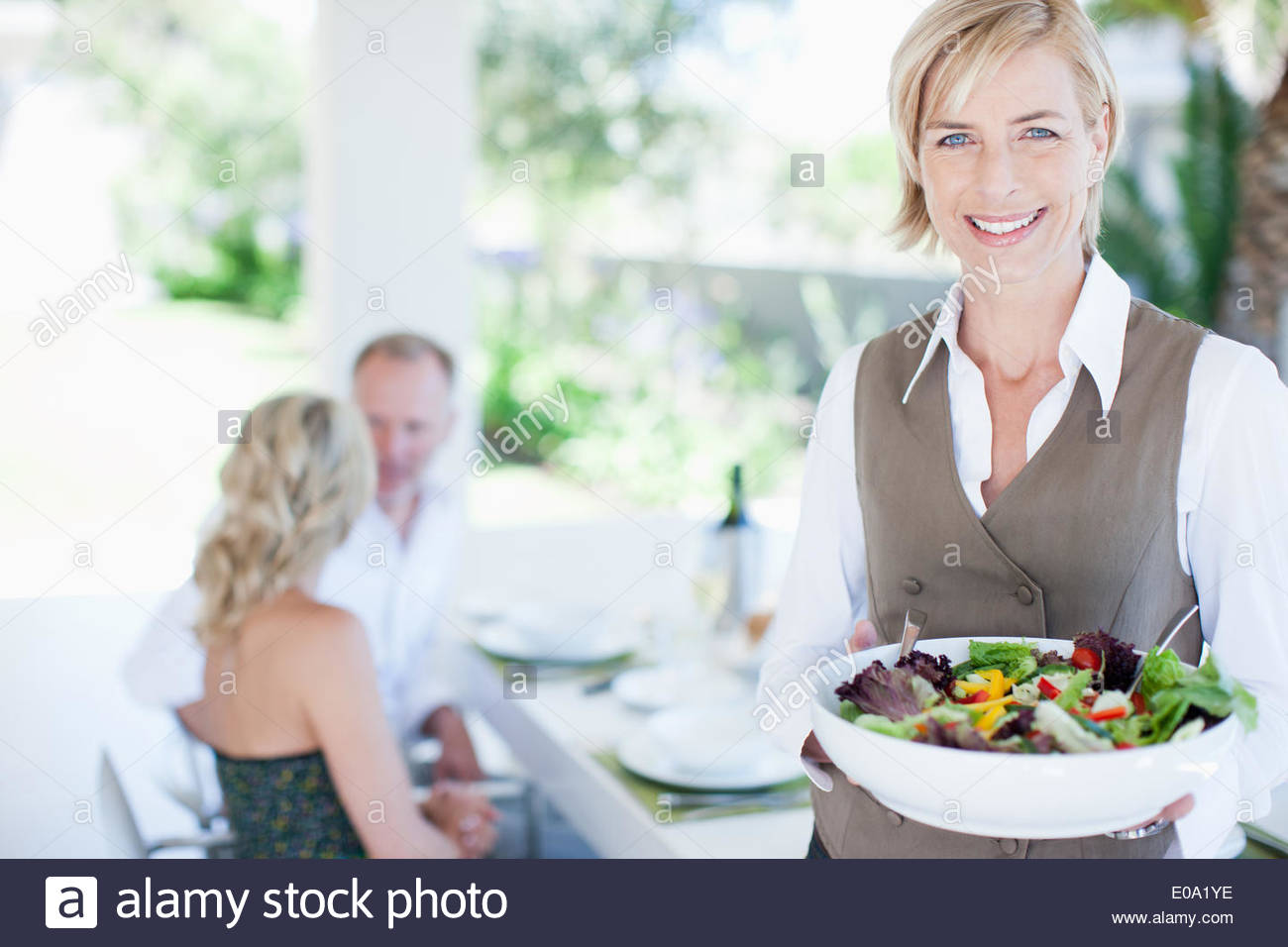 Woman serving salad to friends - Stock Image