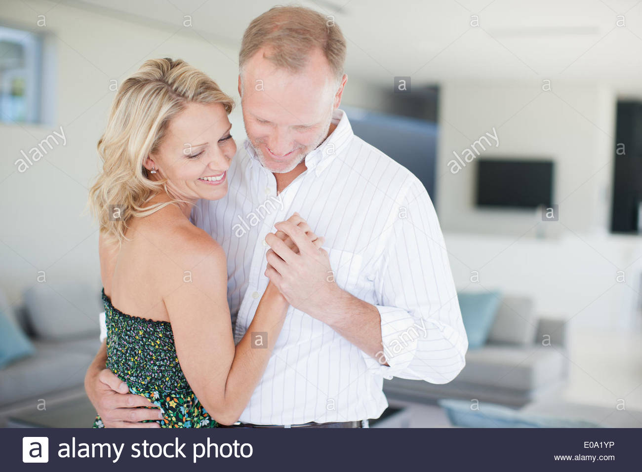 Couple dancing in living room - Stock Image