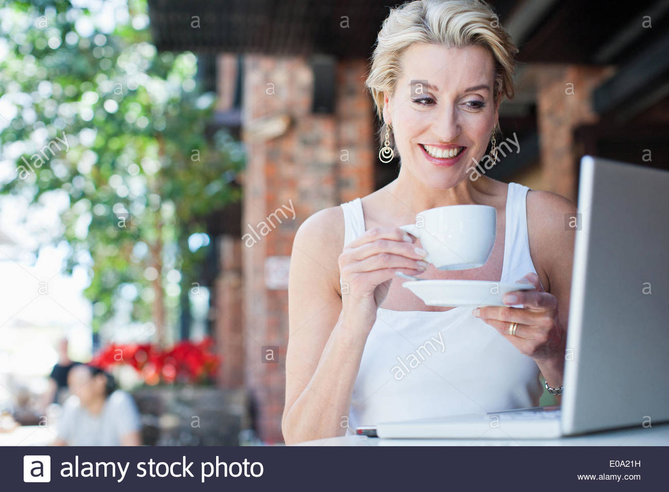 Woman talking on cell phone with coffee and laptop in cafe - Stock Image