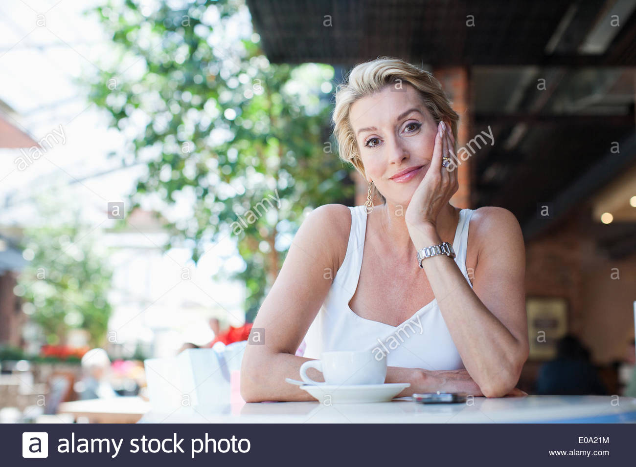 Woman drinking coffee in cafe - Stock Image