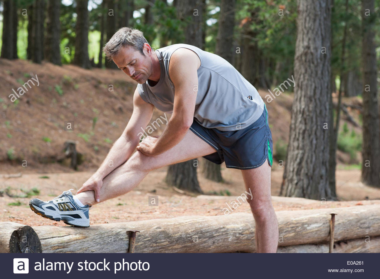 Man stretching before run in forest - Stock Image