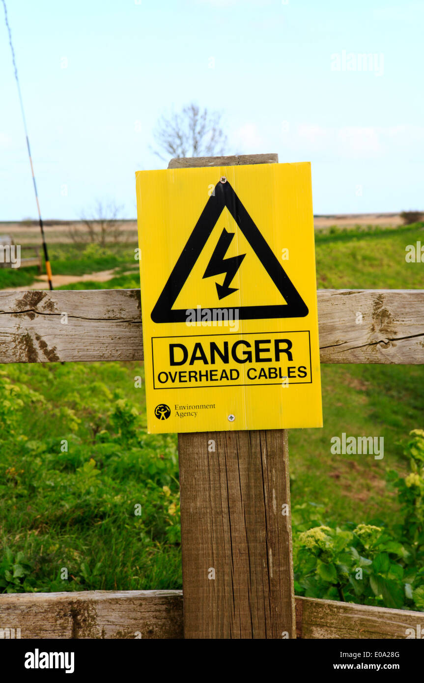 A yellow danger sign warning of overhead cables. - Stock Image